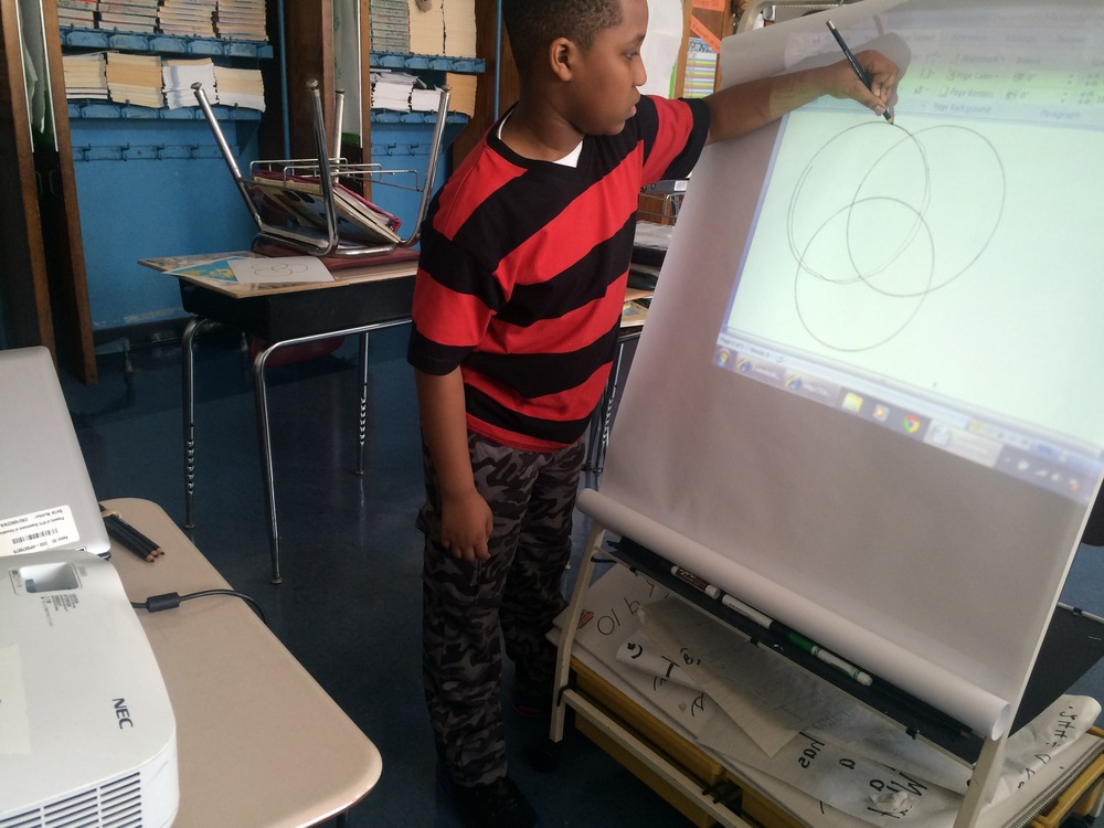 Frank traces 3 interlocking circles to make an illustration for the Learning Wall that shows interdependence.