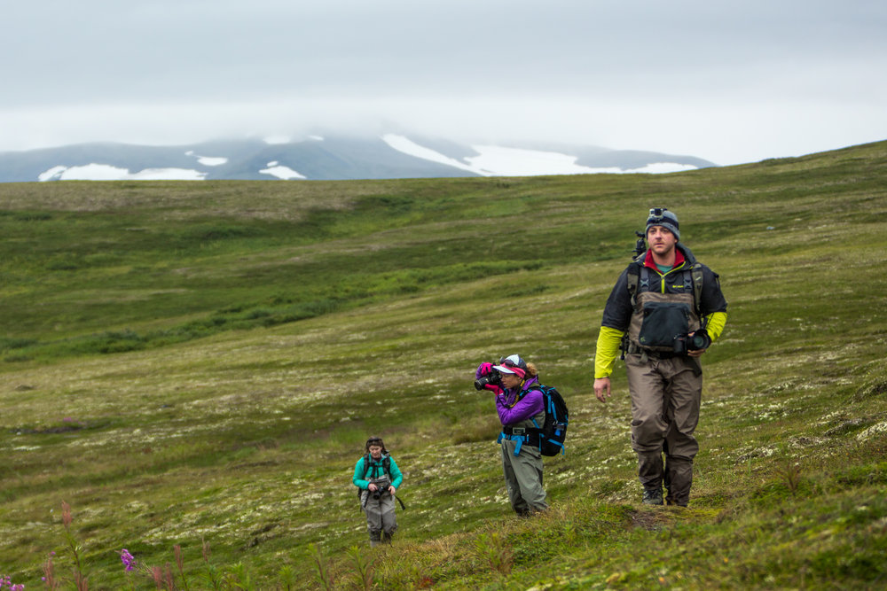 Photographers Andrew Snyder, Jenny Adler, and Gabby Salazar hiking over the tundra
