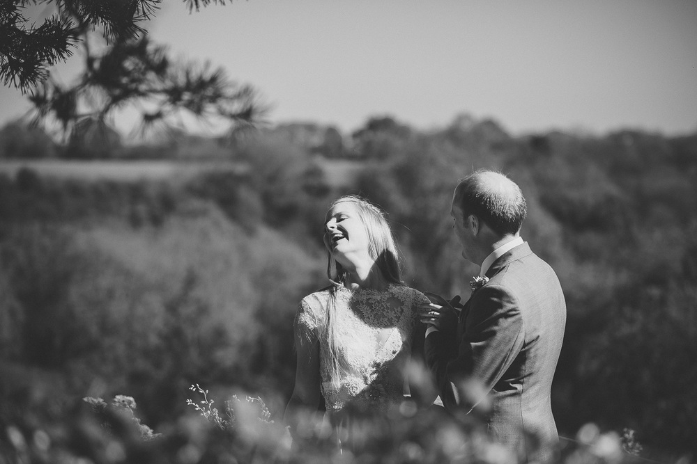 bride laughing with room during romantic couples session at wedding