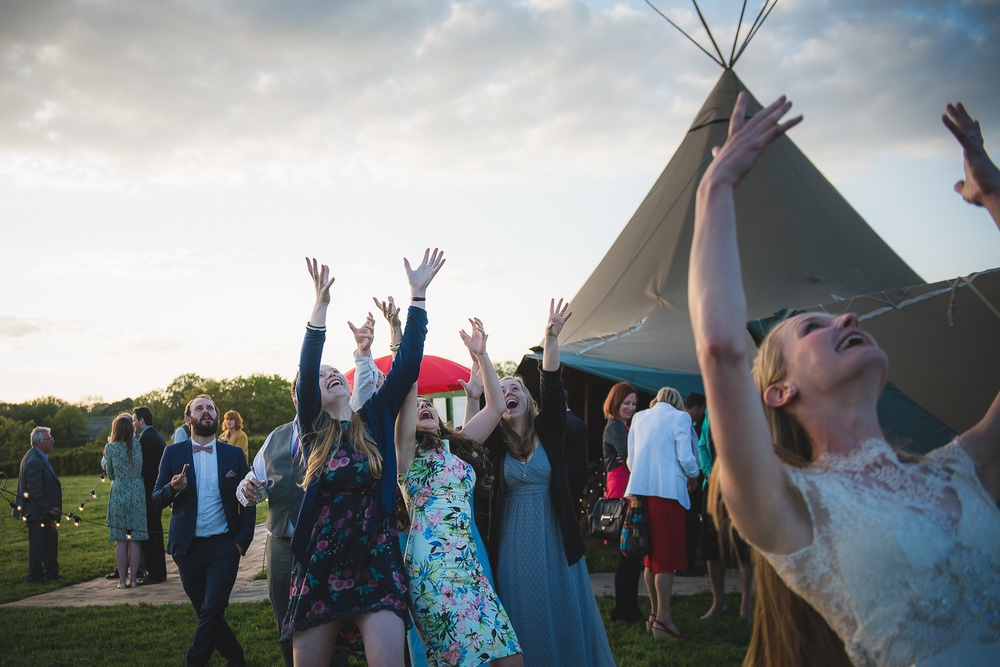 wedding confetti toss in sussex uk with tipi in field