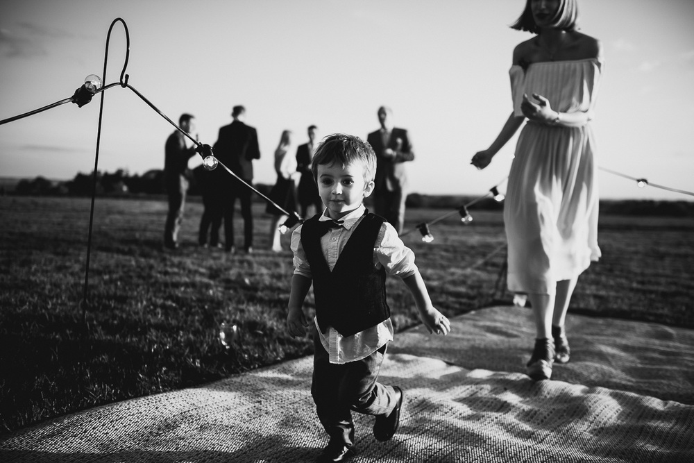 candid wedding picture of child at wedding running from his mother