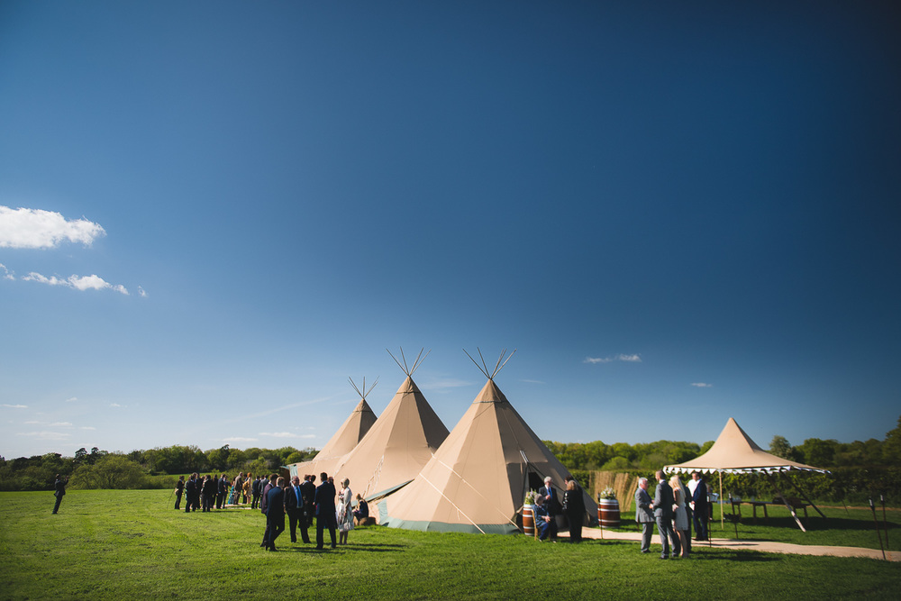 blue sky over tipi at wedding in field