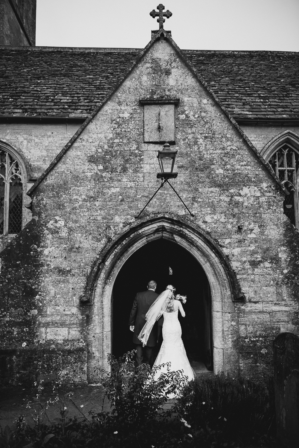 beautiful documentary wedding picture of bride entering old church with father