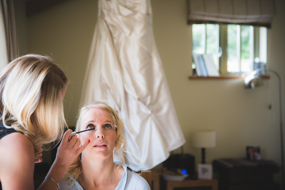 documentary image of bride getting ready with dress hanging