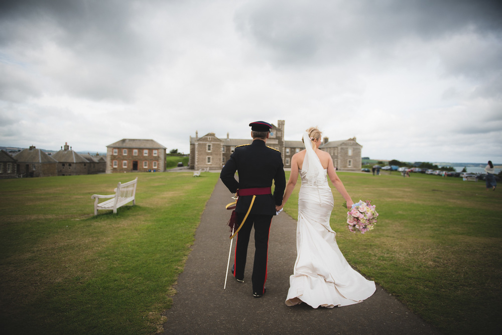 bride and groom walking away from pendennis castle in cornwall