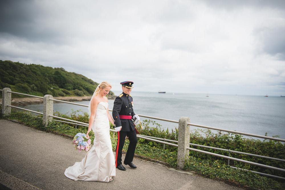romantic documentary image of bride and groom walking by seaside in cornwall