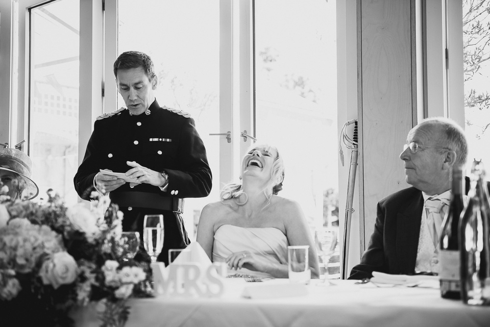 bride laughing at groom's speech during wedding reception in falmouth cornwall