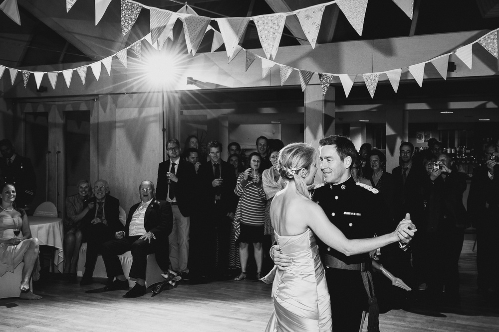 black and white photo of bride and military groom first dance