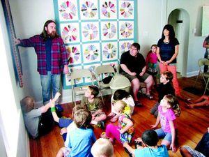 Eliot Reed, left, describes textiles to kids at Park Place Arts. The textile exhibit runs through Aug. 31.
