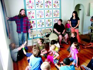 Eliot Reed, left, describes textiles to kids at Park Place Arts. The textile exhibit runs through Aug. 31.