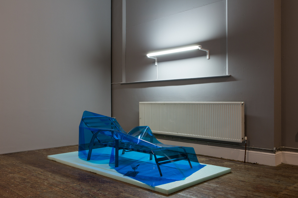 Dominic Samsworth  Condo Glut , 2014 Packing foam. sun lounger, flourescent light, UV lighting, gel, plastic tray, glasses, Dirty martini - Red Hook water, gasoline, abalone shell 26 x 97 x 48 inches