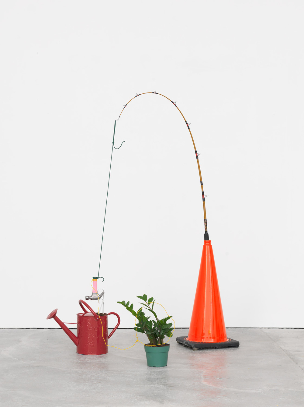 Tropical Tease, 2015 Traffic cone, fishing pole, rope, hammer, shelf bracket, soil, watering can, wire, and potted plant. 67 x 44 x 44 inches