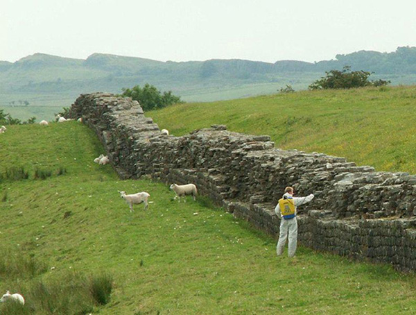 Hadrian's Wall near Birdoswald Fort. The man shown here is spraying the wall with weed killer to protect the landmark from the biological weathering of stones. | Courtesy of Wikimedia Commons