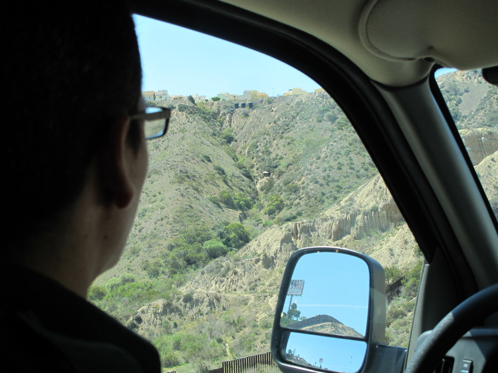"Our driver, a CBP agent, looks out at Smugglers Gulch where a ""spotter's hut"" is nestled in the hillside 