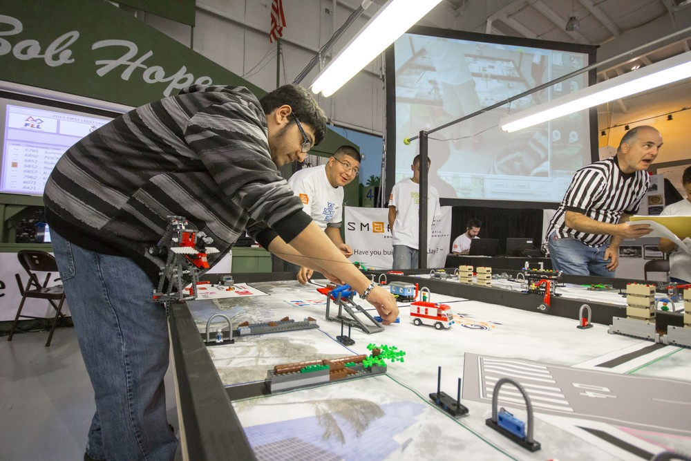 Jose Bermudez and Alan Cabrera reset a competition table for a Lego robot tournament.