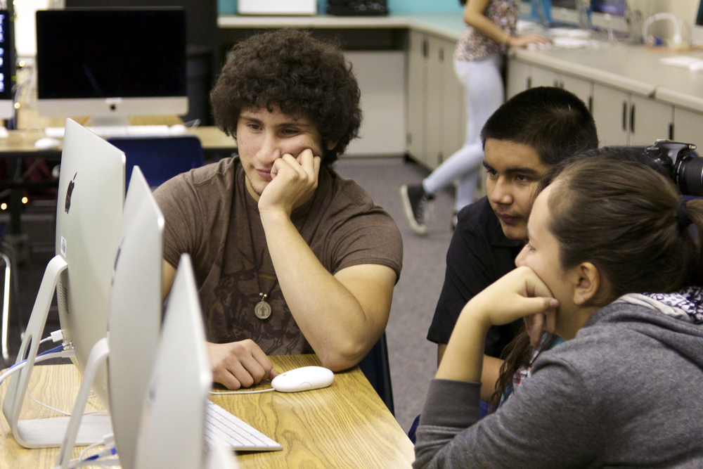Jose Aguirre and Raymond Galeana work on Final Cut Pro X with middle school students.
