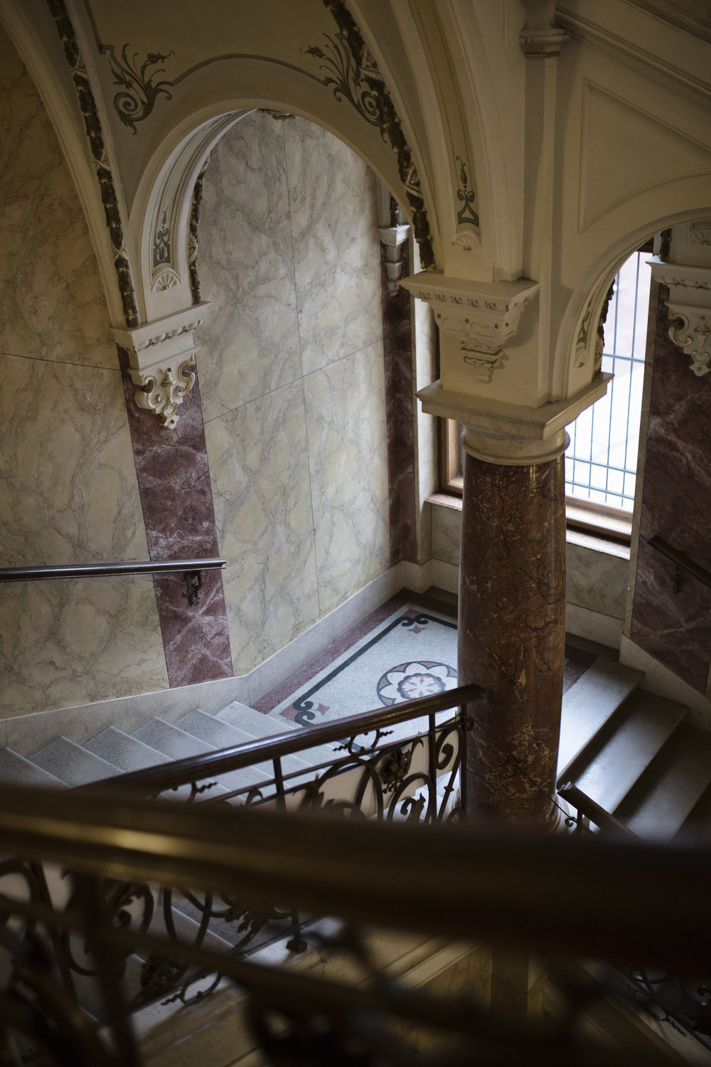 The three-legged staircase with columns of polished red marble is a dominant feature of the building. The railing consists of bronzed blacksmith's bars curled into spirals, finished with scattered acanthus leaves and small rosettes.