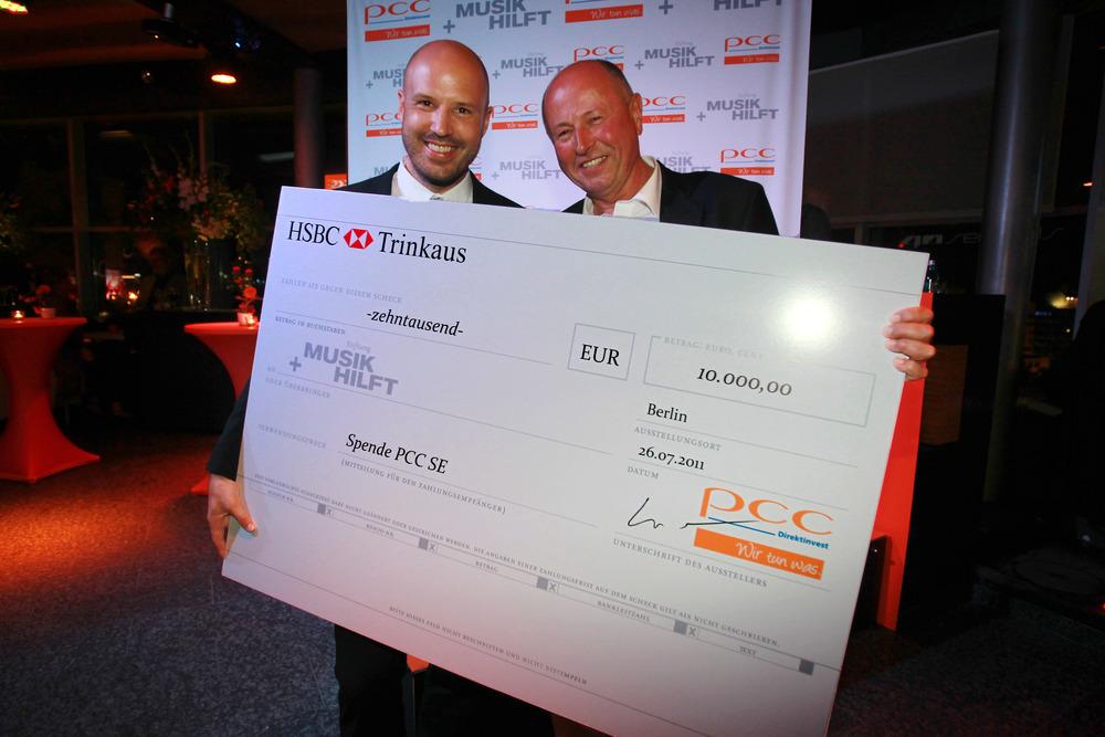 Waldemar Preußner überreicht den Scheck im Wert von 10.000€ an Christopher von Deylen von Musik Hilft (© public adress)