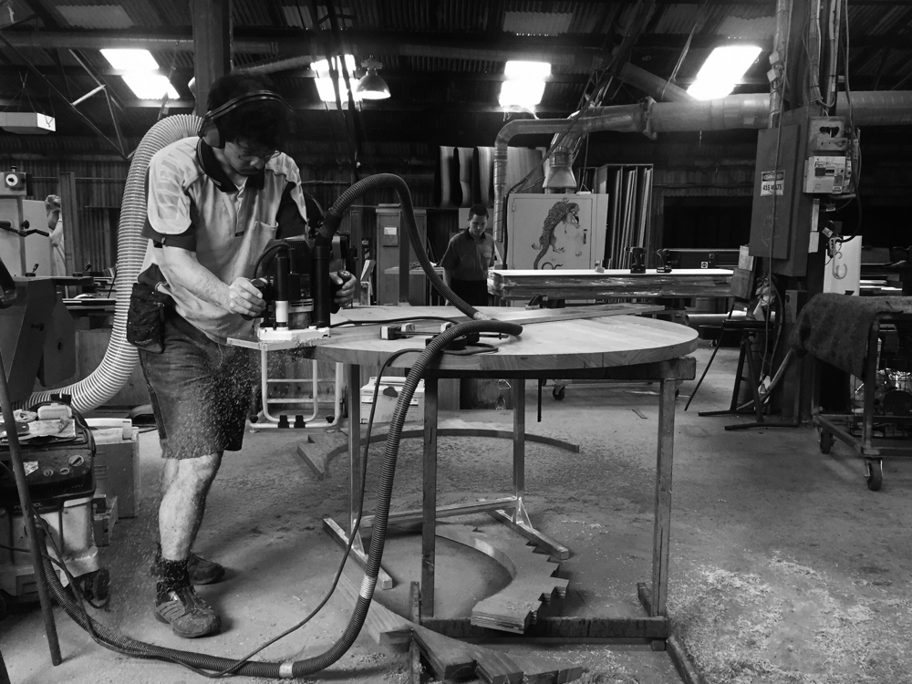 Hiroshi Yamaguchi running an edge profile into salvaged red hardwood for the dowel leg table