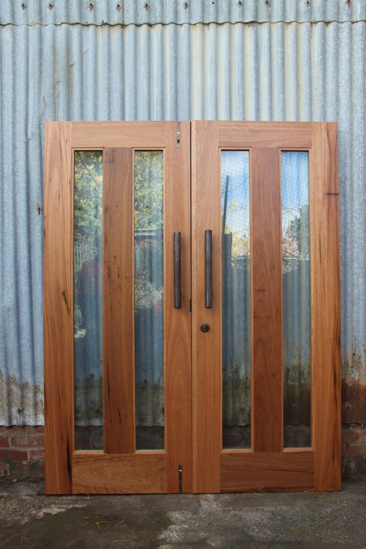 Cleanly finished twin glass panel doors constructed in recycled Blackbutt.