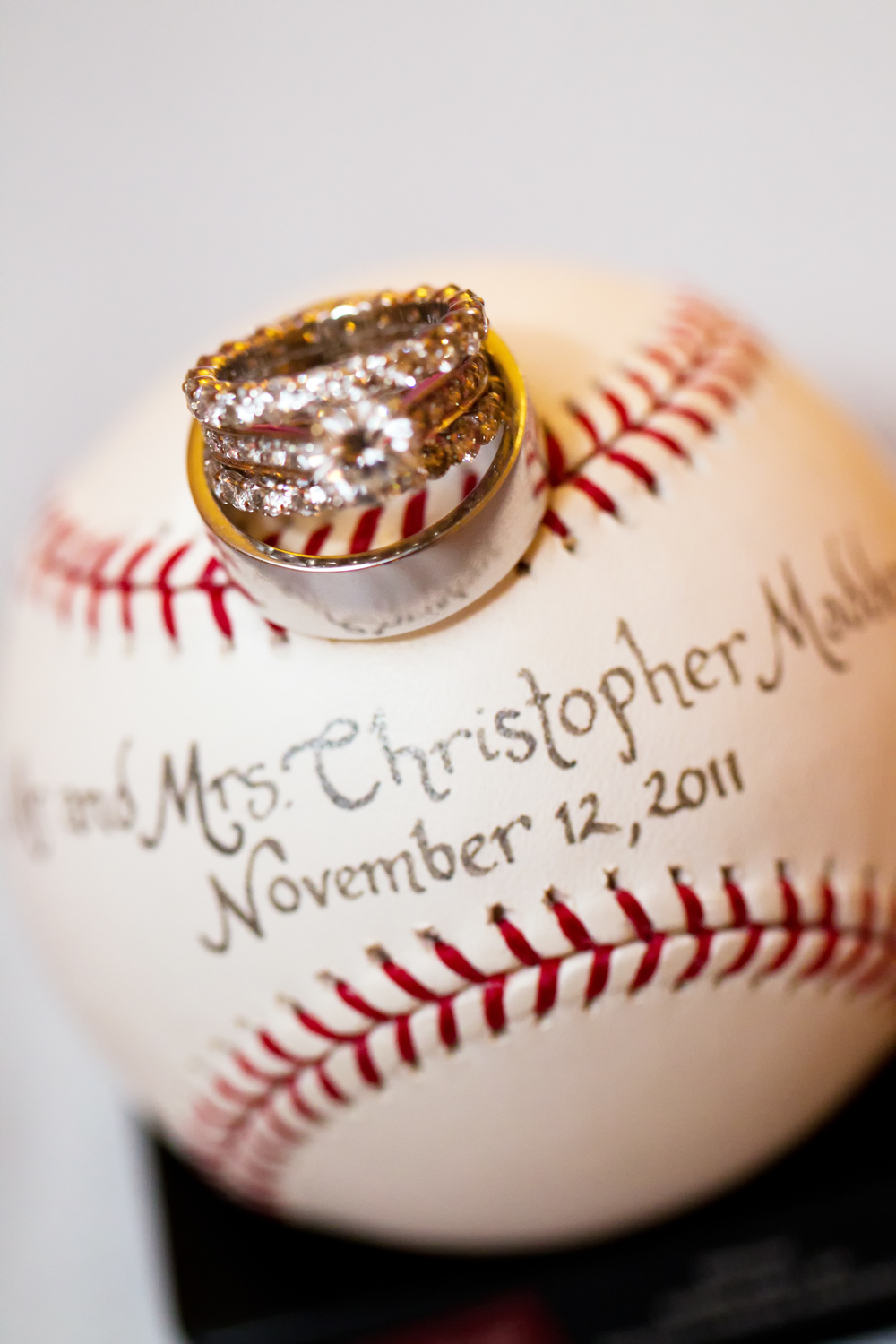 """We love this detail shot of the couple's rings with their """"place card"""" basebell. Photo: Nikki Cole"""