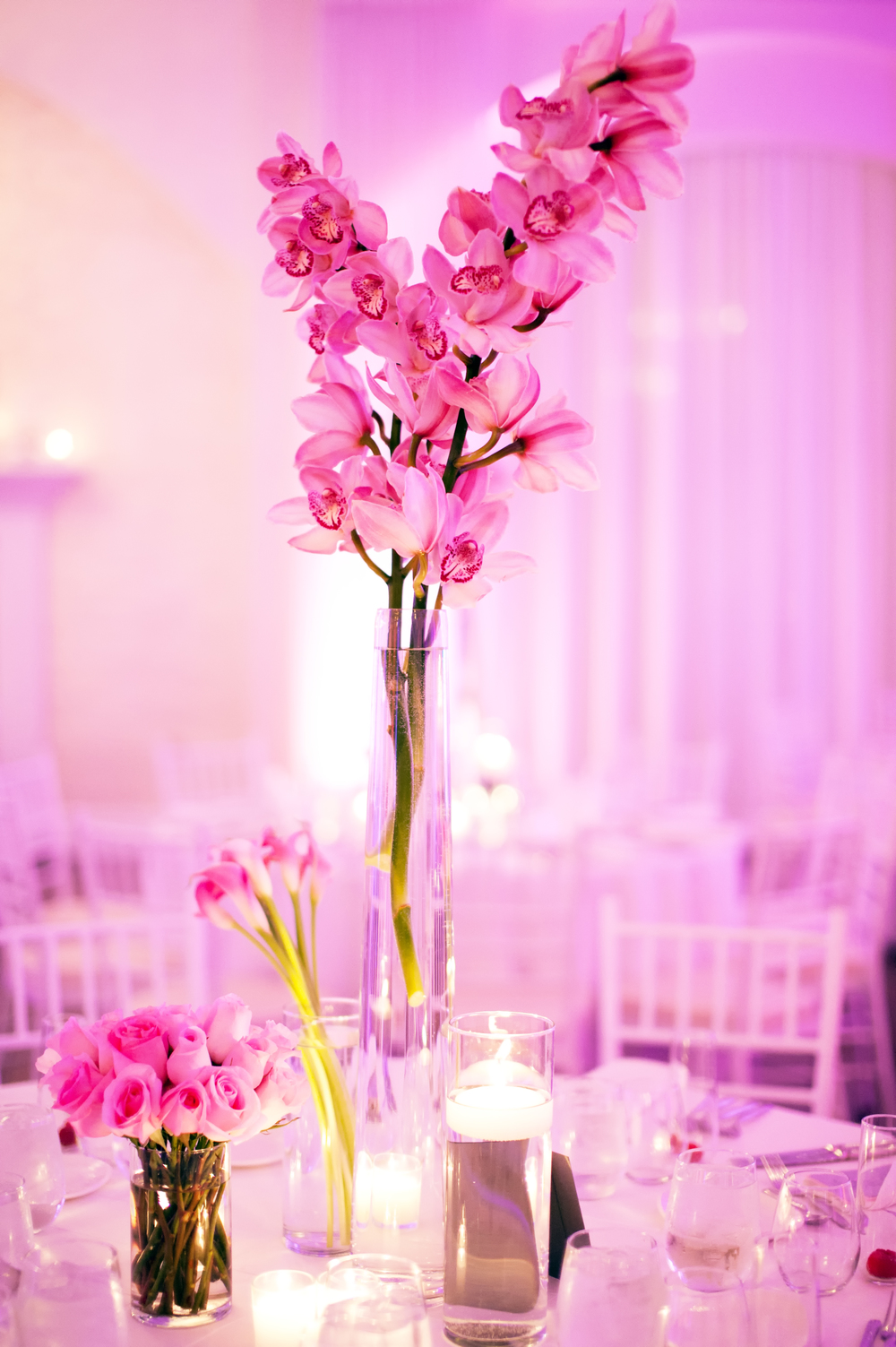 In contrast to one centerpiece of mixed flowers, here's a great example of single variety of a flower in one container at different heights. Add some candles at different heights and the table has a lot of movement. For more pics of this wedding, please click  here.
