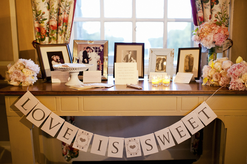 A Blush Pink Paper Banner decorates this beautiful table with family photos of parents, grandparents and great grandparents on their wedding day. Guests can leave their wishes to the bride and groom on squares of paper using our signature ribbon pens! For more pics, click  here .