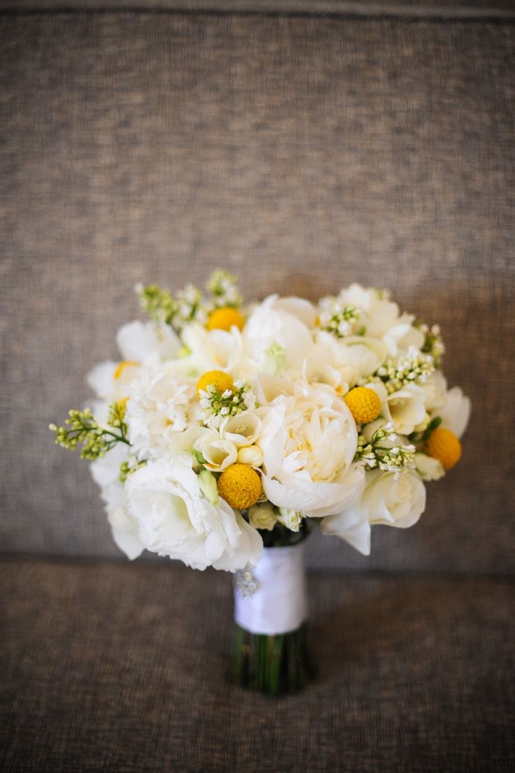 This lovely wedding bouquet featuring butter yellow peonies, freesia and pom poms is just gorgeous!