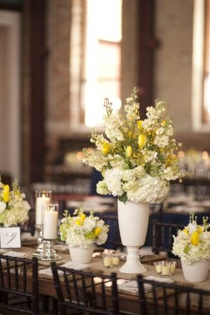 We love this mix of pale yellow and white flowers with the long tables and dark wood. Breathtaking!