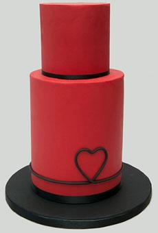 Red can be a tough color for cakes. This modern red wedding cake looks amazing! We love the tall tiers and simple heart design. If there was a way to get a bite of it through the pic, we'd SO want to do it!
