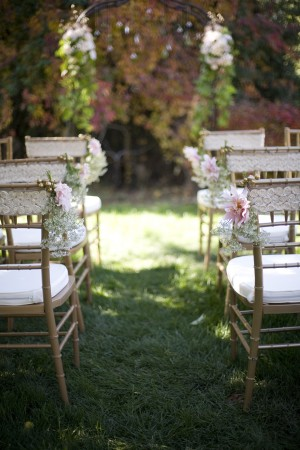 This lace detail on the wedding ceremony chairs is so sweet and perfect!