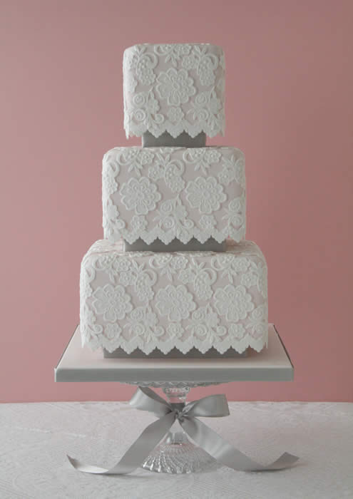 Lace lends itself very well to a cake design. Make sure you have a talented cake artist that can replicate your lace AND transport the cake without any issues! We love the clean lines of this square tiered edible beauty!