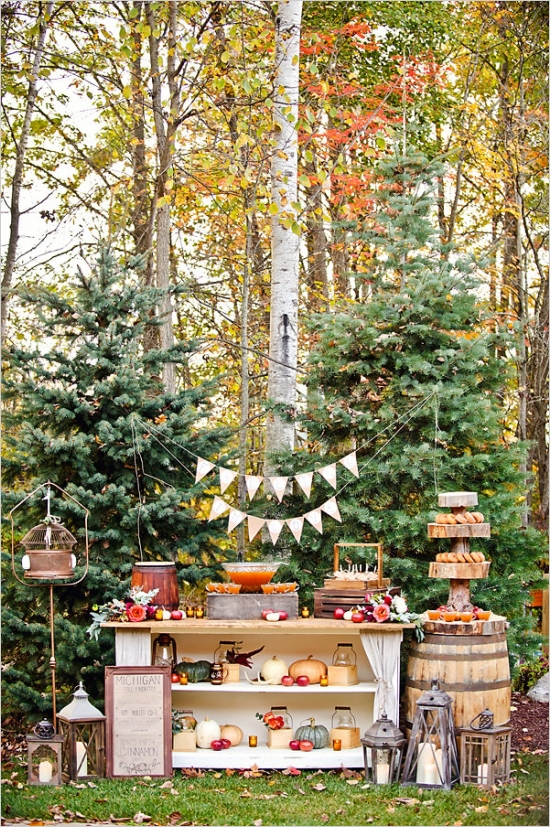 Autumn Wedding Dessert Table  - the back drop of the beautiful trees is stunning and then to add an entire rustic dessert display takes our breath away! We love love LOVE the cider donuts on the rustic cake stand with cups of cider. YUM!