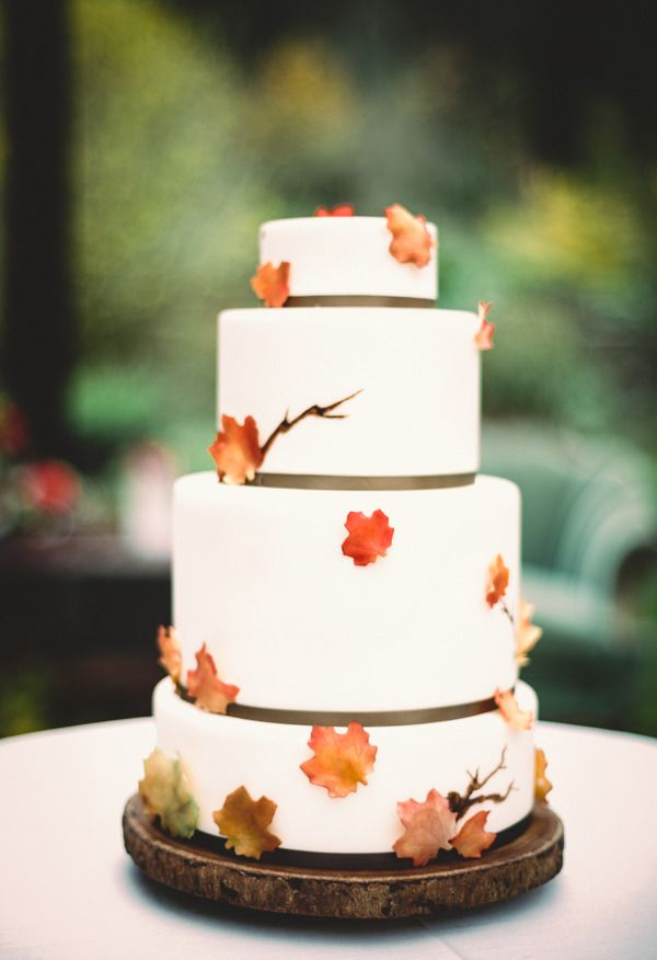 Autumn inspired Wedding Cake  - We love the restraint on this beautiful wedding cake with its coordinating tree trunk inspired base. We love that there are only a few leaves that are created so perfectly that they look real. Sometimes less truly is more.