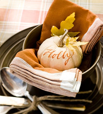Pumpkin Place Card  - We love getting a small pumpkin and writing the guest's name in a Sharpie. Nothing could be easier.