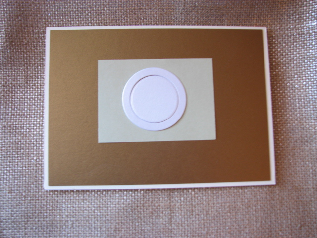 "I used my trusty double-sided tape gun and affixed the gold cover stock on the card. Then I put a 2' x 3"" sage green ""placemat"". I used a clear glue to affix the circles to make the ""plate."""