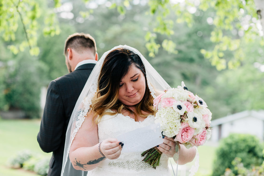 Lyndsay + Michael exchange hand-written notes during their first moment at their Warren Conference Center and Inn wedding (Ashland, MA)