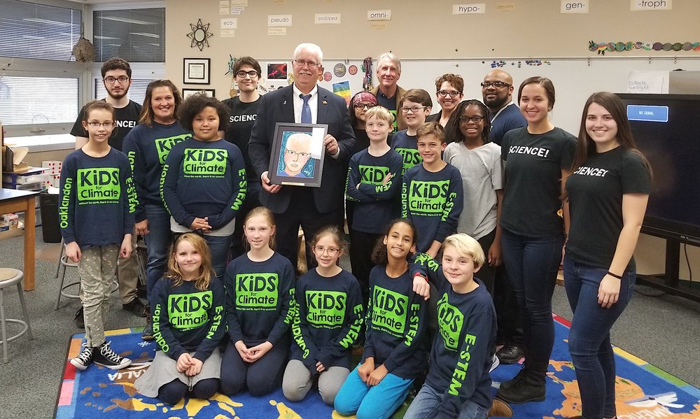 Mayor Collier, holding portrait, is surrounded by Kids for Climate, school officials, and IUPUI students.