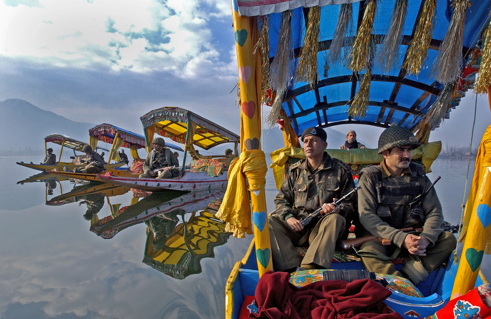 Indian Border Security Force Officers patrol the picturesque Dal Lake in the summer capital of  Srinagar in the Indian held state of Kashmir, February 19, 2002.  Once a tourist hotspot, the only  visitors to this magnificent landscape these days are Indian soldiers. (Ami Vitale)