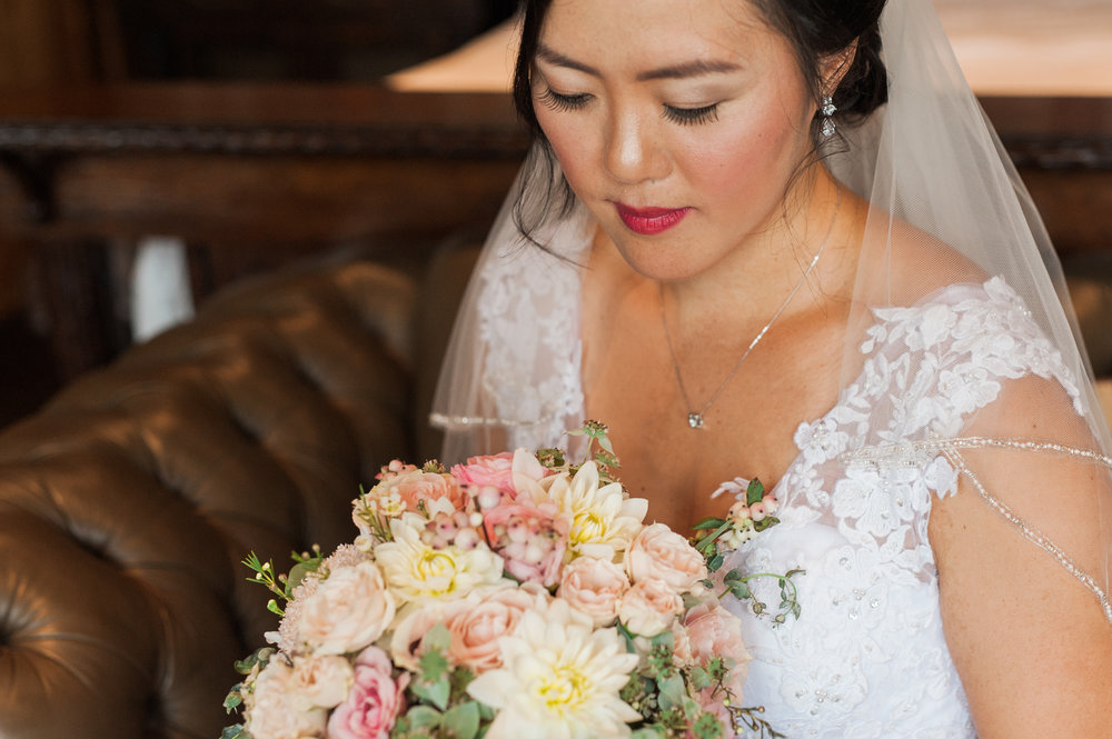 Bride looking at her beautiful summer bouquet.