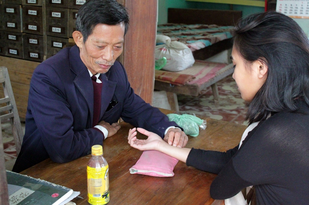 Karen C. with a traditional Vietnamese healer learning how to read pulses for signs of illness.