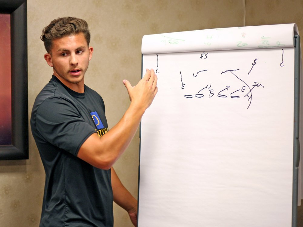 Quarterback Coach Daxx Garman breaks down a play during a recent DeBartolo Sports quarterback training event.