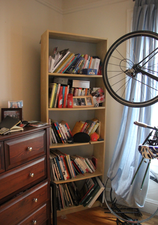 Before:  The corner of the bedroom is overwhelmed by visual clutter on the dresser surface and haphazard bookshelf.