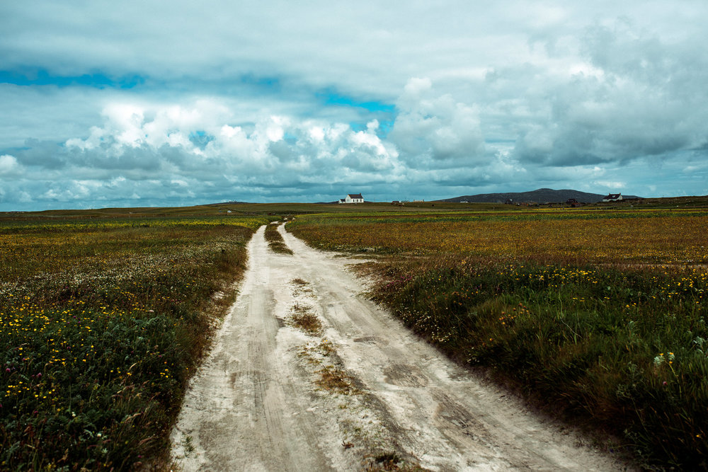 In South Uist, a sandy path winds through the Machair which stretches as far as the eye can see.