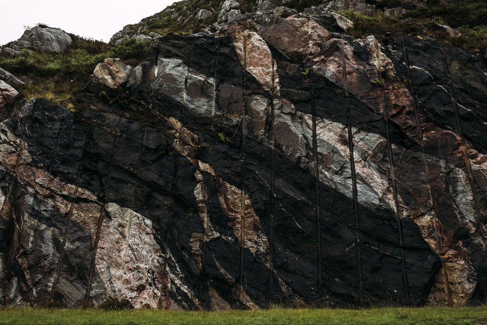 'Pale grey gneisses represent original rock into which once molten sheets of dark basaltic magma were later forced. The streaks of pink granite must be the youngest of the three rock types since they can be seen cutting through both of the older types.'