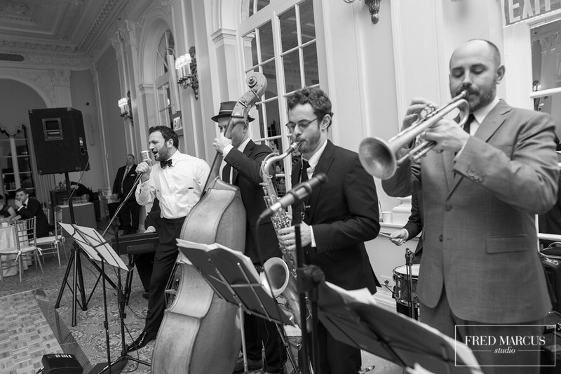 The groom sits in with the band at a wedding reception at the Yale club in new york city