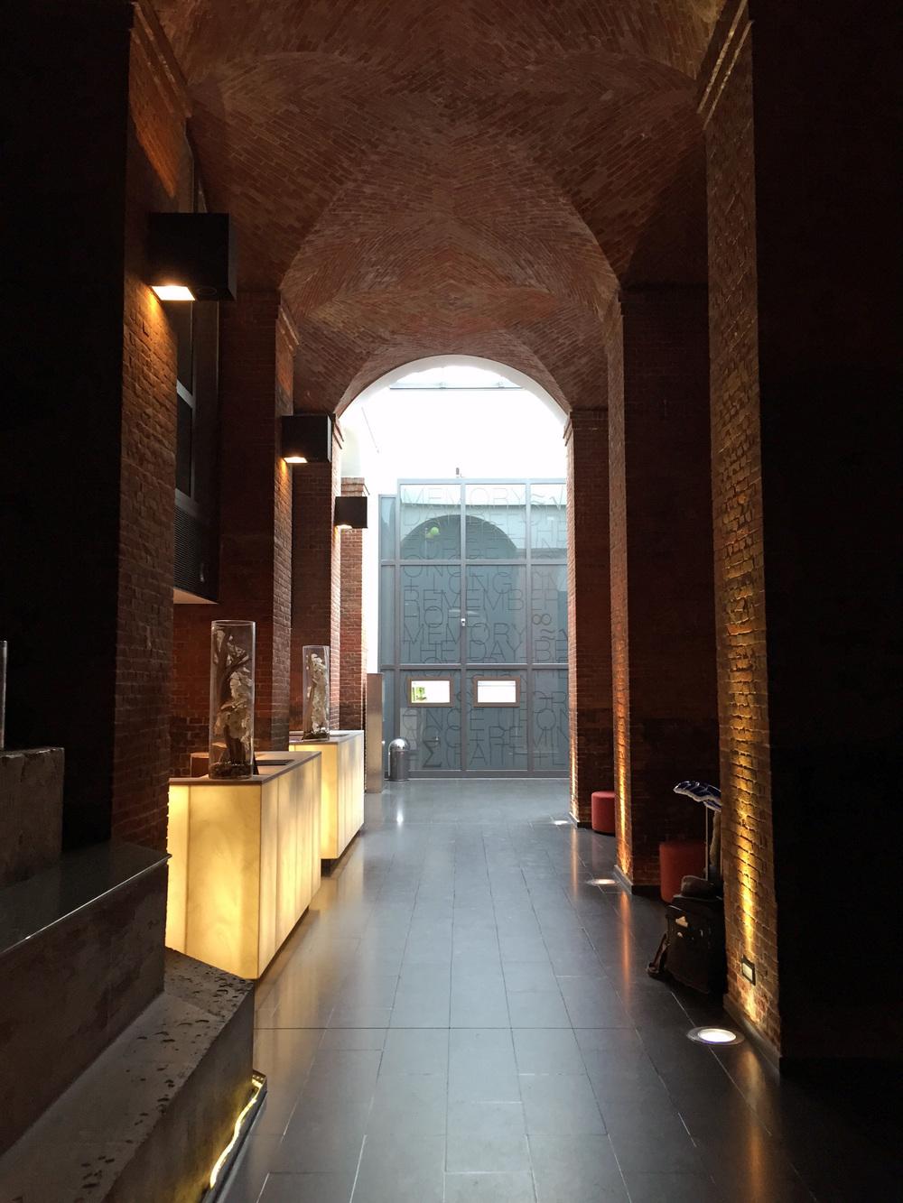 """Blick in Richtung Rezeption mit dem acht Meter hohen Backsteingewölbe. Im Hintergrund sieht man eine von der Künsterlin Ulrike Böhme gestaltete Glaswand """"Memory""""."""