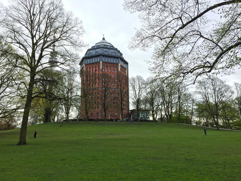 Wasserturm mit Schanzenpark. Im Hintergrund sieht man den von Bäumen verdeckten Fernsehturm.
