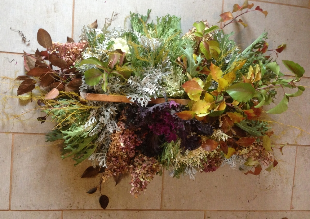 flowering kale, dusty miller, hydrangea, leafy branches, and asparagus fronds in vintage berry basket.