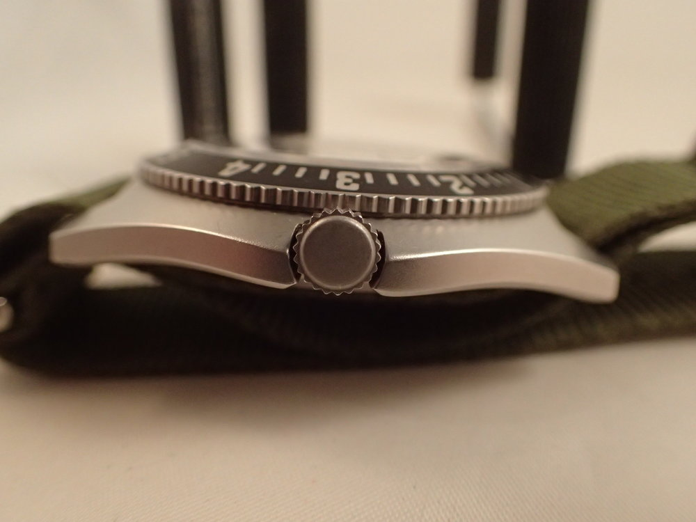 The case profile and 12-hr bezel are classic asymmetric Navigator.